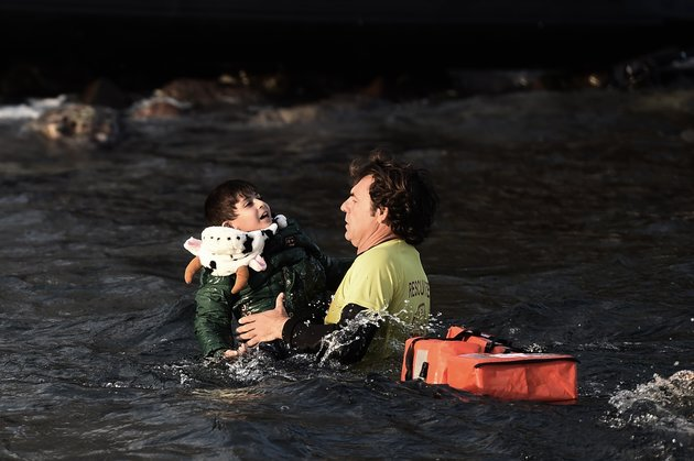 A Spanish lifeguard saves a migrant child as the boat he had boarded with other migrants and refugees sinks off the Greek island of Lesbos after crossing the Aegean sea from Turkey on October 30, 2015. AFP PHOTO / ARIS MESSINIS (Photo credit should read ARIS MESSINIS/AFP/Getty Images)
